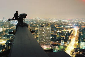 Edgework: An urban explorer straddles a building maintenance unit on top of an unfinished luxury residential development in East London. Photo: Theo Kindynis.